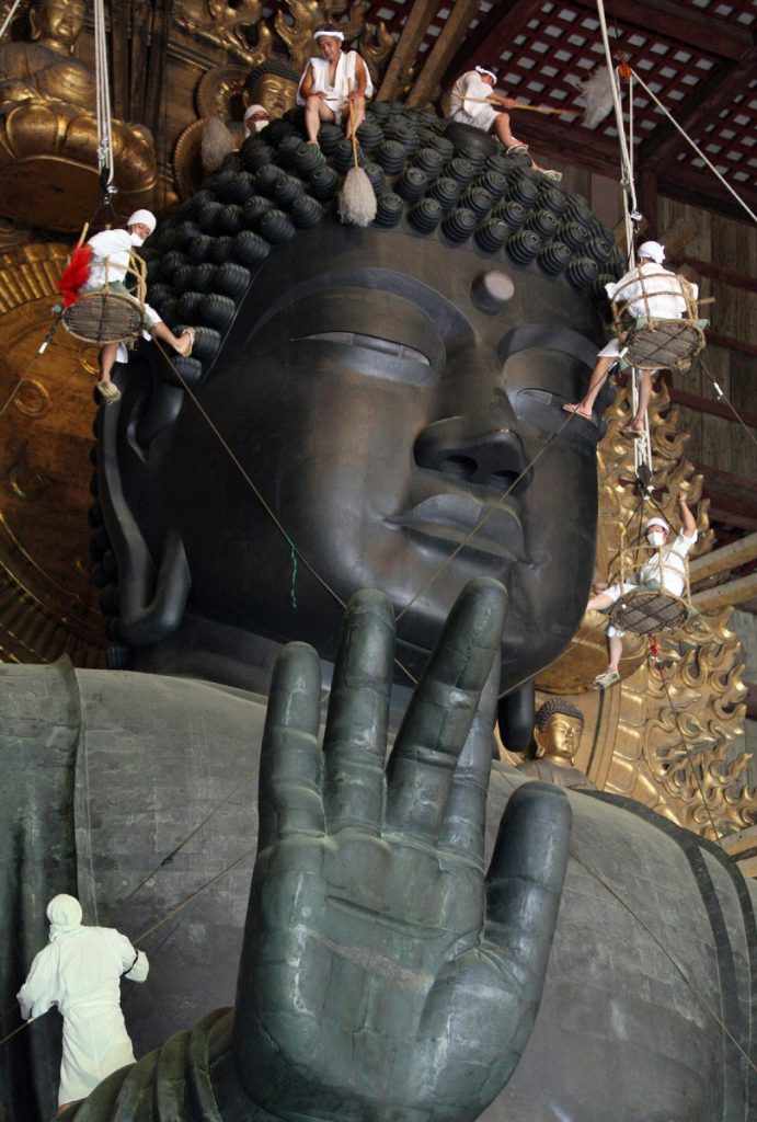 Some 150 Buddhist monks and believers in white costumes wipe and sweep the 15-meter-tall Great Buddha statue which was built in 752 AD, at Todaiji Temple in Nara, western Japan. Monks and volunteers cleaned a year's worth of grime from the Great Buddha for the annual sprucing up as the rirual cleaning.